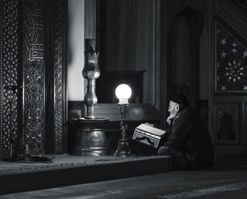 An elderly man reading Quran in a mosque as part of his worship.